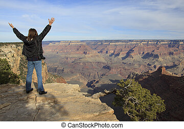 a woman holds her arms up in wonder at the sight of the grand canyon