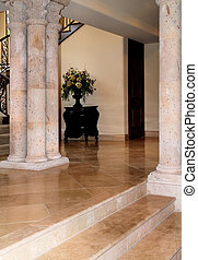 private home with large stone columns and travertine floors