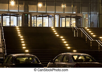 grand entrance in modern office building at night, two cars on parking