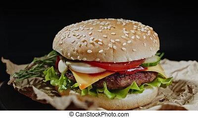 grand, hamburger, romarin, mayonnaise, fromage, appétissant, isolé, parchment., viande, fondu, sauce, salade verte, sombre, légumes, fond, tourne, fumée, vue, oignon, hamburger, côtelette, gros plan