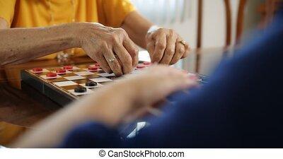 grand-mère, jouant vérificateurs, jeu société, à, petite-fille, chez soi