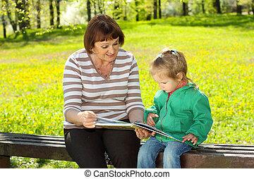 grand-mère, petite-fille, livre lecture, dehors