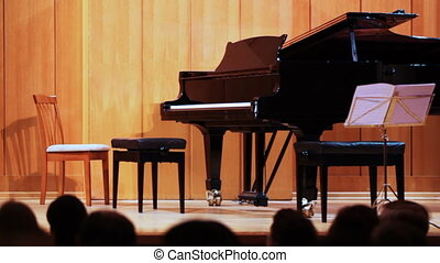 grand piano on stage, people in hall wait for appearance of musician
