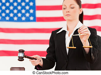 grand plan, de, a, jeune, juge, frappement, a, marteau, et, tenue, balances justice, à, une, drapeau américain, dans, les, fond