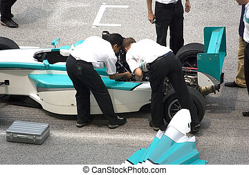 Stalled grand prix car being repaired at the starting grid.