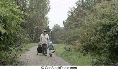 Grandad and grandson walking in the countryside. Old man rolling a trolley bag, little boy holdinga toy car.