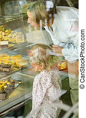 Grandchild and grandmother looking at cakes cafe window...