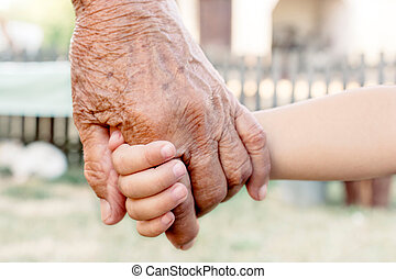 Grandchild and grandparent - Grandchild holding grandparent...