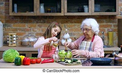 Grandchild girl helps her granny to cook - Little grandchild...