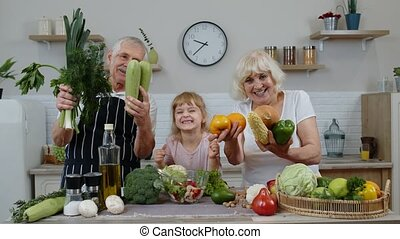 Grandchild girl with senior grandparents recommending eating...