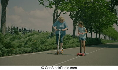 Grandchild teaching grandmom to ride scooter in park