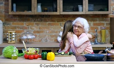 Grandchild with granny having fun and embracing while...