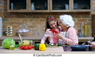 Grandchild with granny having fun while cooking at home