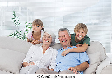 Grandchildren and grandparents sitting on couch