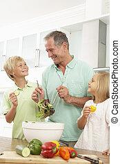 Grandchildren Helping Grandfather To Prepare Salad In Modern Kitchen
