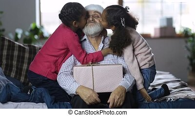 Grandchildren kissing grandfather with xmas gift - Two...