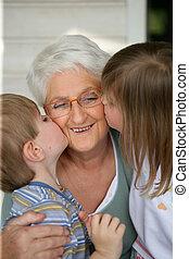 Grandchildren kissing grandma