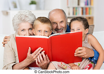 Grandchildren reading with their grandparents - Cute little...