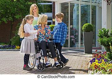 Grandchildren visiting grandmother in wheelchair
