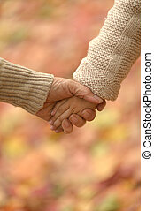 Granddaughter and grandmother holding hands close up