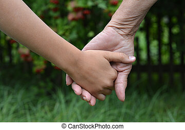 granddaughter and grandmother holding hands outdoors close up