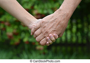 Granddaughter and grandmother holding hands outdoors close-up