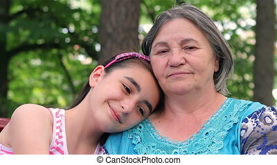 Granddaughter and grandmother smiling at camera in a park.