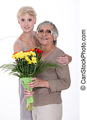 Granddaughter and grandmother with flowers