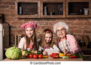 Granddaughter and grandmother with tablet searching recipe