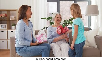 granddaughter giving flowers to grandmother - family,...