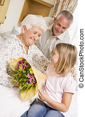 Granddaughter Giving Flowers To Her Grandmother In Hospital