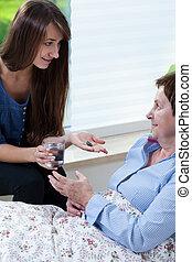 Horizontal view of granddaughter giving grandma medicines