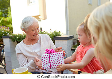 granddaughter giving present to grandmother