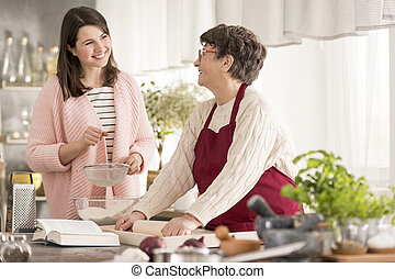 Granddaughter helping grandma in a kitchen