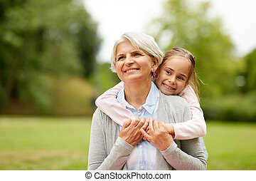 granddaughter hugging grandmother at summer park