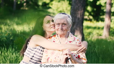 Granddaughter hugs her grandmother and kisses her on the cheek