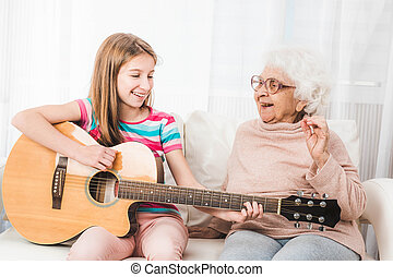 Granddaughter playing on guitar for grandmother