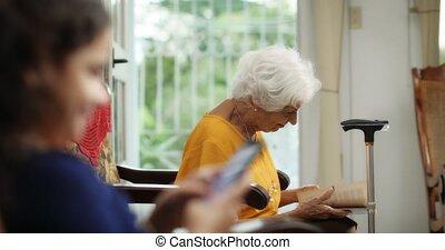 Granddaughter Using Mobile Phone Smartphone Telephone And Grandma Reading Book
