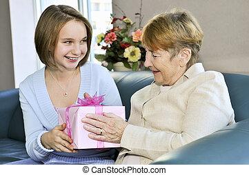 Granddaughter visiting grandmother - Granddaughter bringing...