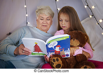 Granddaughter with grandmother watching a picture book
