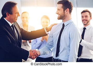 grande, job!, dois, alegre, homens negócio, apertar mão, enquanto, seu, colegas, aplaudindo, e, sorrindo, em, a, fundo