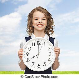 grande, menina sorridente, segurando, relógio