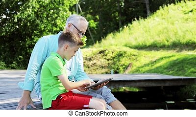 grandfather and boy with tablet pc on river berth 31 -...