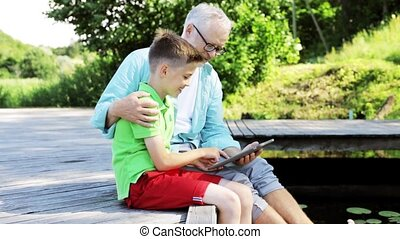 grandfather and boy with tablet pc on river berth 34 -...