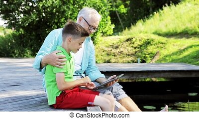 grandfather and boy with tablet pc on river berth 35 -...