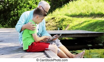 grandfather and boy with tablet pc on river berth 33 -...