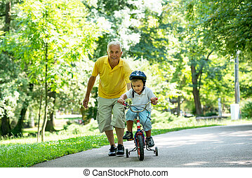grandfather and child have fun in park - happy grandfather ...