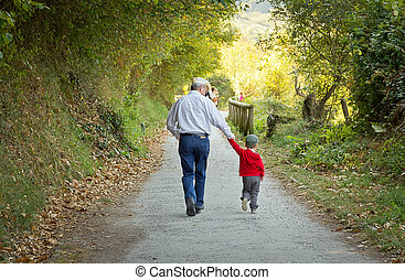 Grandfather and grandchild walking in nature path
