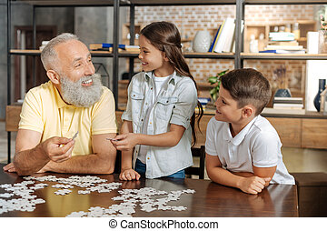 Grandfather and grandchildren assembling jigsaw puzzle altogether