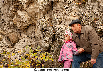 Grandfather and granddaughter near stone wall